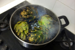 Globe artichokes being cooked in hot water Stock Photo
