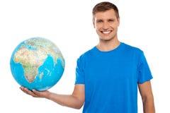 Globe attrayant de fixation de jeune homme dans sa main Photographie stock libre de droits
