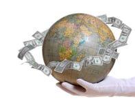 Globe avec de l'argent en orbite à disposition avec le gant Photographie stock