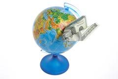 Globe avec l'avion d'origami fait à partir du dollar d'isolement sur le blanc Images libres de droits