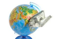 Globe avec l'avion d'origami fait à partir du dollar d'isolement sur le blanc Photo libre de droits