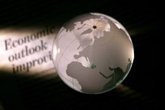 Economy Outlook Improving. Globe with the background of newspaper headline Stock Photos