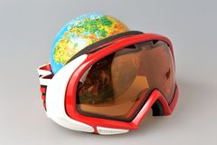Globe behind mountain ski mask on gray Royalty Free Stock Images
