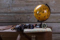 Globe with binoculars on suitcase. Stock Photos