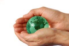 Globe bleu sur des mains photos stock