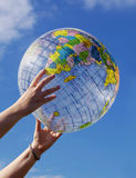 Globe in blue sky. Hands holding Earth globe in bright blue sky Royalty Free Stock Photography