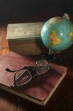 Globe with book and eyeglasses. Stock Images