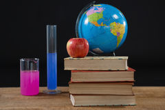 Globe and books stack with apple on top against black background Royalty Free Stock Photo