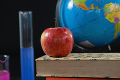 Globe and books stack with apple on top against black background Royalty Free Stock Image