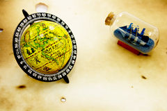 Globe and bottle with ship. Grunge background Royalty Free Stock Images
