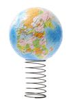 Globe bouncing on metal spring. Conceptual image of globe showing Europe, Africa, and Asia bouncing on metal spring reflecting the state of economy Royalty Free Stock Photos