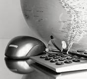 Globe and calculator. Image of a calculator with mouse and globe on a table Royalty Free Stock Photo