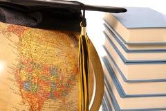 Globe, capuchon de graduation et livres antiques Photo stock