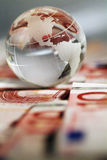A globe and cash money closeup. Royalty Free Stock Image