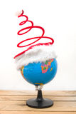 Globe with christmas hat. On wood table Royalty Free Stock Image