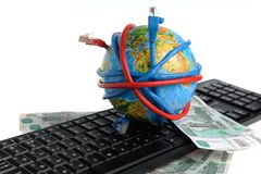 Globe coiled wires, banknotes on the keyboard Royalty Free Stock Photography