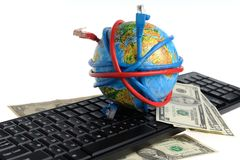 Globe coiled by wires, dollars on the keyboard. On a white background Royalty Free Stock Photo