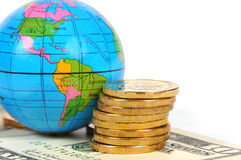 Globe, coins and dollars Stock Image