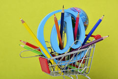Globe, colored pencils and at sign in a shopping cart Royalty Free Stock Image