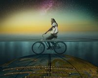 Surrealistic composition - a cyclist riding on the globe under w royalty free stock photography