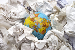 Globe among crumpled papers Stock Photos