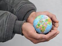 Globe dans des mains de l'homme Photographie stock libre de droits
