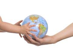 Globe dans des mains de la chéri. Images stock