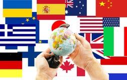 Globe dans des mains sur un fond des drapeaux de partout dans le monde Photographie stock
