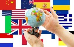 Globe dans des mains sur un fond des drapeaux de partout dans le monde Photographie stock libre de droits