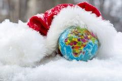 Globe dans le chapeau neigeux de Santa Claus Photos libres de droits