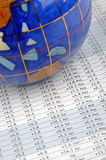 Globe and data sheet. A colorful globe and a sheet with many data, means world wide economy statistic, calculation, analysis and other business concept Stock Photo