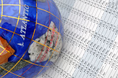 Globe and data sheet. A colorful globe and a sheet with many data, means world wide economy statistic, calculation, analysis and other business concept Royalty Free Stock Images