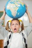 Globe de équilibrage d'élève mignon sur la tête dans une salle de classe Photos libres de droits