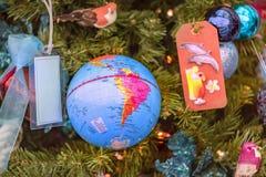 Globe de globe accrochant sur un arbre de nouvelle année comme jouet d'arbre de Noël photographie stock