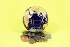Globe de bleu et d'or se reposant sur une pile d'un mélange des pièces de monnaie des USA l'Europe et Grande-Bretagne photos stock