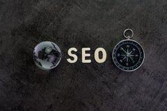 Globe de décoration, alphabet SEO et boussole sur le chalkb foncé de ciment Images stock