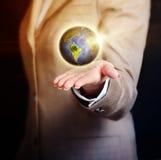Globe de la terre de fixation de femme d'affaires dans sa main Images libres de droits