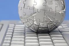 Globe de puzzle en métal sur le clavier d'ordinateur Images stock