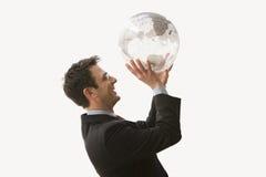 Globe de sourire de fixation d'homme d'affaires photographie stock libre de droits
