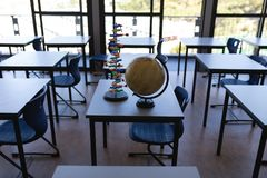 Globe and DNA model for children on a table. Surface level of a globe and a DNA model immobile on a table in an empty classroom stock photos