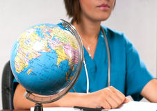 Globe and doctor. Globe in front of a medical doctor Royalty Free Stock Photo