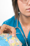Globe and doctor. Doctor with finger on the globe on white background Stock Photography