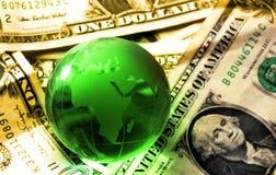 Globe dollars. Green crystal  globe on dollar bills globalization concept warm light Stock Photography