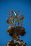 Globe en métal d'or se reposant sur le radier de béton fleuri Photographie stock