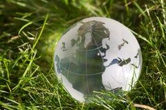 Globe en verre dans l'herbe Photographie stock libre de droits