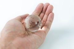 Globe en verre dans la paume Photographie stock libre de droits