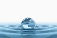 Globe en verre de la terre dans l'eau Photographie stock libre de droits