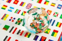 Globe en verre sur les drapeaux Images stock