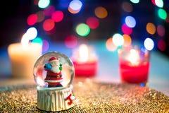 Globe et bougies de neige de Santa sur le coloré Images libres de droits