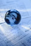 Globe with financial papers. Glass globe with North America and business papers royalty free stock image